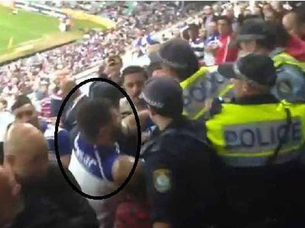 BAD FORM: A Bulldogs fan 'throws a punch' at a policeman as fans clash with officers after their NRL loss to the Sydney Roosters.