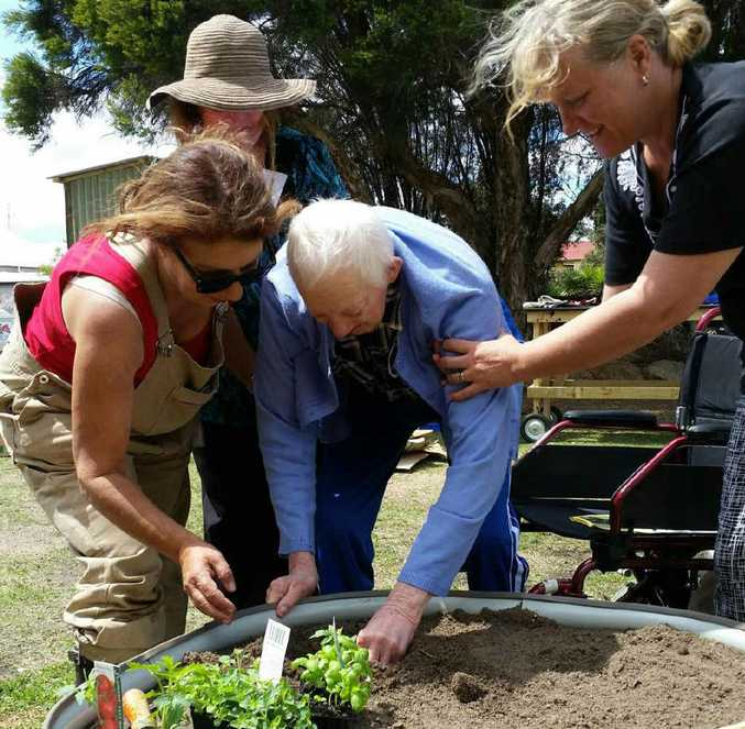 Staff and volunteers help The Oaks Nursing Home resident Joe Boston at the Warwick Victory Community Garden.