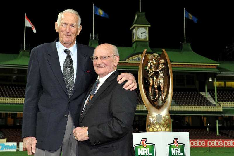 Former rugby league players Norm Provan (left) and Arthur Summons re-create their iconic €˜Gladiators image that was taken 50 years ago, at the SCG in Sydney, Wednesday, Aug. 21, 2013. The premiership trophy, formally known as the Telstra Premiership Trophy, has been renamed the Provan Summons Trophy in their honour.