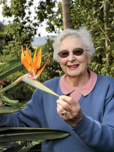 Dr Betty Marks, in her garden, shows off a bird of paradise.