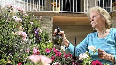 Gloria Hurst watering her garden.