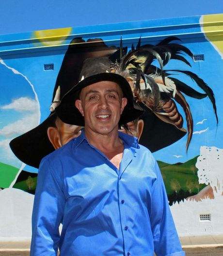 Nick Christodoulou in front of his portrait on the new Faces of Toowoomba mural.