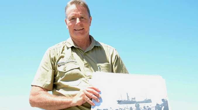 Bryson Coverdale of Gold Coast Tweed Tours displays an historical photo at Point Danger.