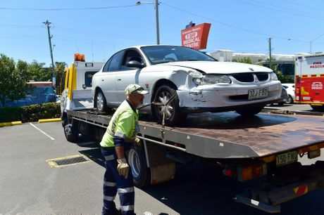 Tow truck drivers remove a car from the Chemmart Kawana Waters pharmacy shopfront.