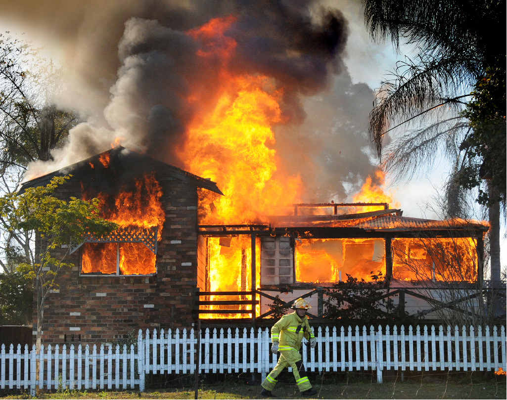 UP IN FLAMES: A Gympie Fire and Rescue officer rushes off to retrieve more hoses as a blaze takes hold of an Old Goomboorian Rd home in August, 2008.