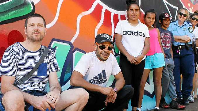 COLLABORATION: INTRA Youth Service's Paul Phillips, Aboriginal artist Lewis Henson and Senior Constable Lisa Paice, youth case manager at PCYC Lismore, have been working on a mural with Goonellabah kids. Inset is the public PRIDE mural near the transit centre in Lismore.