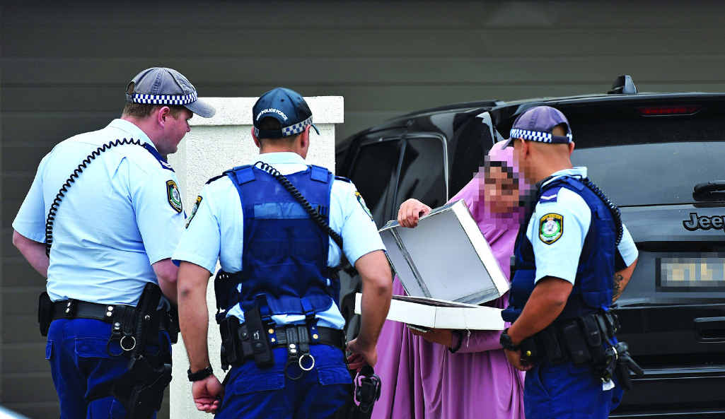 STRESSFUL TIME: NSW Police officers question the occupant of a Merrylands house raided yesterday morning.