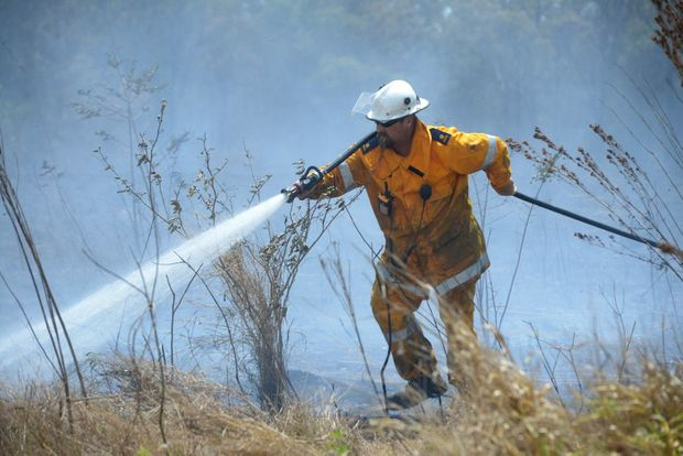 BUSHFIRE: Emergency services fight to contain a bushfire near Coonarr. Fanned by strong westerly winds the fire moved rapidly towards Goodwood Road, putting homes and farms at risk. Photo: Max Fleet / NewsMail