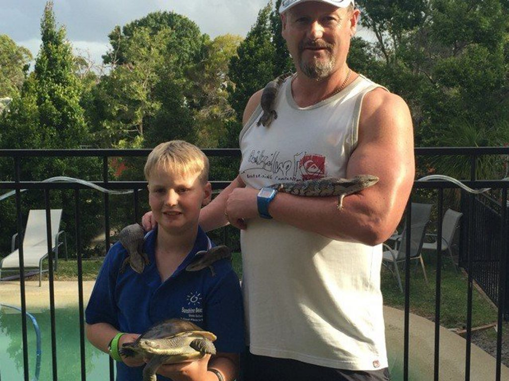 Noosa Heads eight-year-old Leroy Brown and his dad Ray Brown hold some of the reptiles that live at their home.
