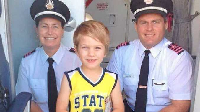 IN THE AIR: Chase Standley, pictured with staff from Qantaslink, who took him on a tour of a plane ahead of his first flight to Brisbane.