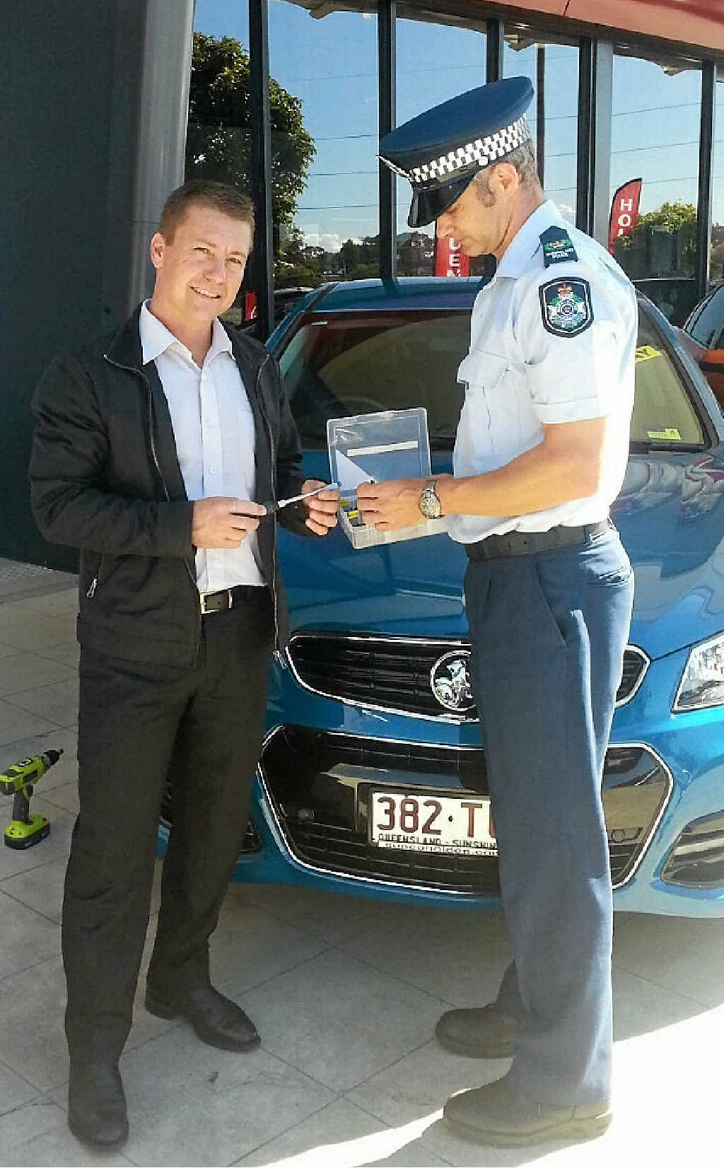 CO-OPERATION: Sunco Motors general sales manager Ky Vogler and a police officer discuss ways of minimising vehicle number plate theft.