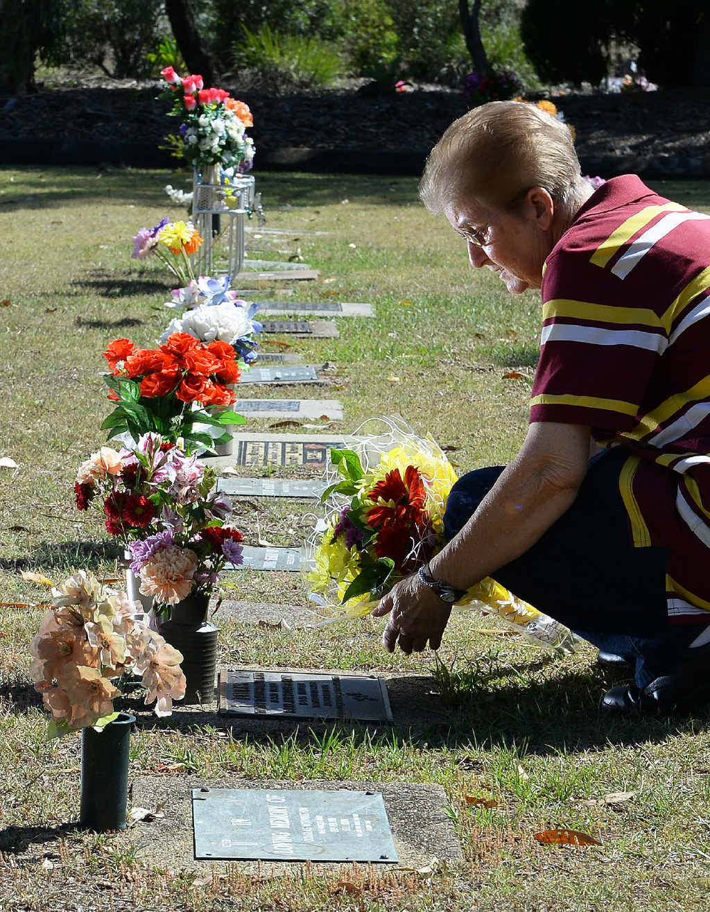 RAW EMOTION: Joy Faulks placing flowers at her children's grave sites.