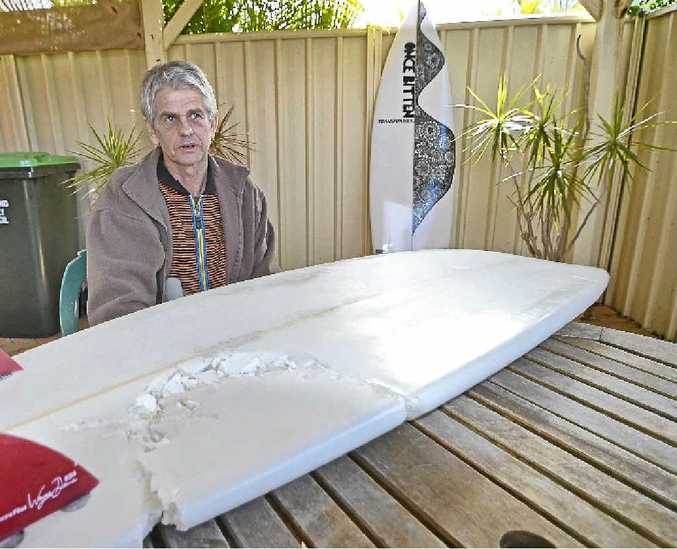 ONCE BITTEN: Evans Head resident Craig Ison with the board he was riding when he was attacked by a great white shark at Main Beach.