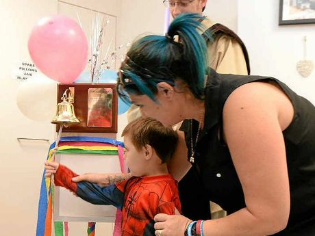 Ben Jessen, 5, pictured with his mother Renee rings a bell denoting that he has completed his last round of chemotherapy at the Rockhampton Hospital. The bell has been donated to the hospital by the Jessen family.