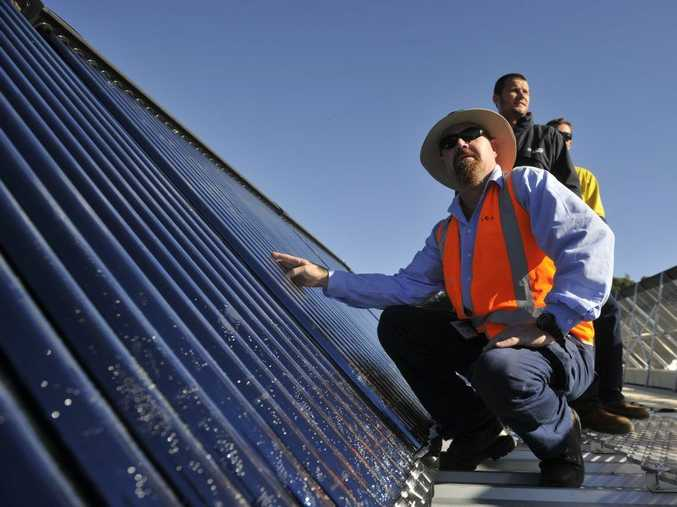 (From left) Lismore City Coucncillor Steve Dillon, Laser Plumbing construction manager Jake Campbell, and Laser Plumbing Site Supervision Brett Eaglesham on the roof of the Memorial Baths where the new solar water system has been installed. Photo Marc Stapelberg / The Northern Star