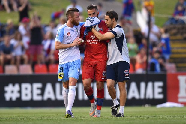 Shane Smeltz of Sydney gestures to Mark Birighitti of the Jets as he is escorted from the field after clashing with Smeltz while making a save at Hunter Stadium in Newcastle. (AAP Image/Dan Himbrechts)