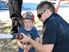 FIREFIGHTERS: Ewan Coban, 3, learns the ropes from firefighter Troy Hart.