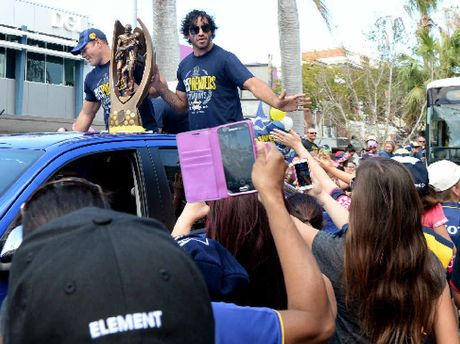 Cowboys players Matt Scott and Johnathan Thurston wave to fans as they head along Victoria St during their tickertape parade in Mackay.