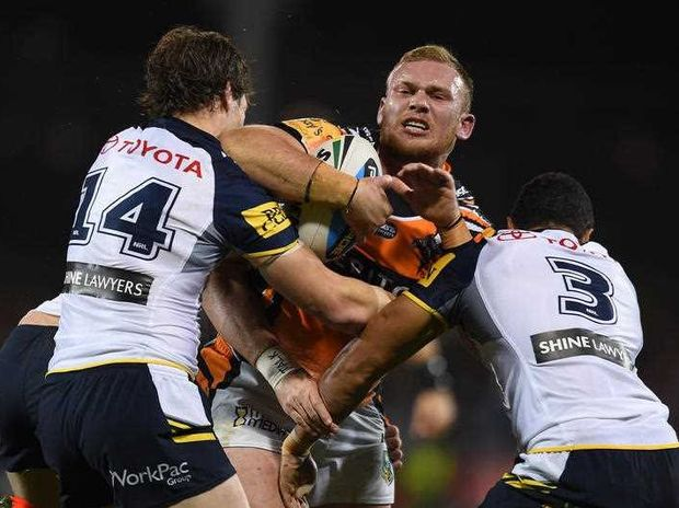 Matthew Lodge of the Tigers is tackled by Rory Kostjasyn (left), and Justin O'Neill of the Cowboys during the Round 11 NRL match between the Wests Tigers and the North Queensland Cowboys, at Campbelltown Stadium, Sydney, Saturday, May 23, 2015.
