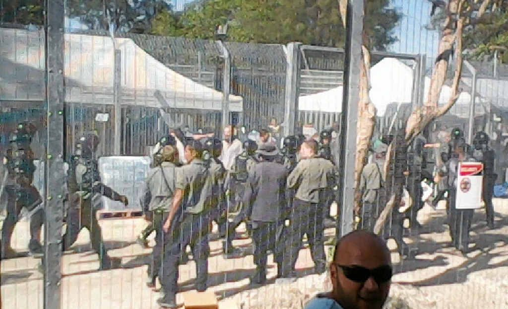 BARS AND WIRE: Security forces gather at the Manus Island detention centre during a hunger strike in January.