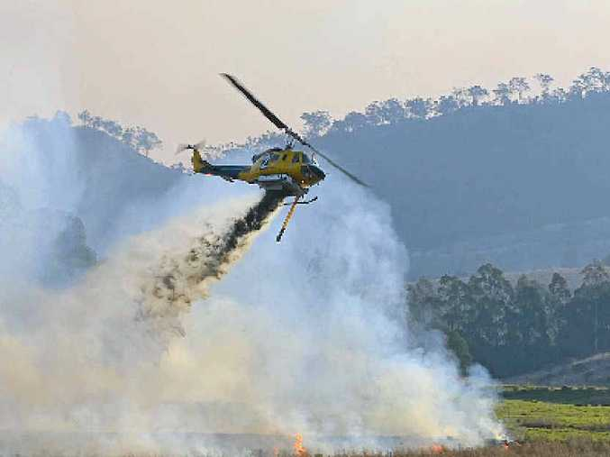 SAFETY FIRST: Multiple water bombing helicopters and firefighters helped control a rapid bush fire threatening houses on the Clifton-Gatton Rd, Hirstglen.