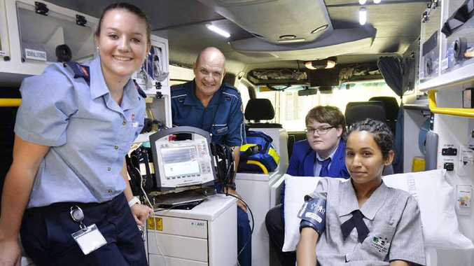 INSPIRING FAMILY: Father and daughter, Ross and Annabelle Muller, show Bundamba High School student Dipanshu Sharma, 15, and St Peter Claver College student Daniel Andrew, 17, through an ambulance at the Ipswich Hospital.