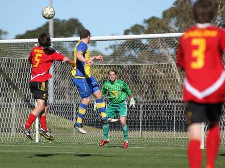 Soccer, Sunshine Coast Fire v's Brisbane Strikers at Stockland Stadium: Fire keeper, Antony Hall (in green), looks on as his captain, Greig Henslee, leaps to head a ball in defence.