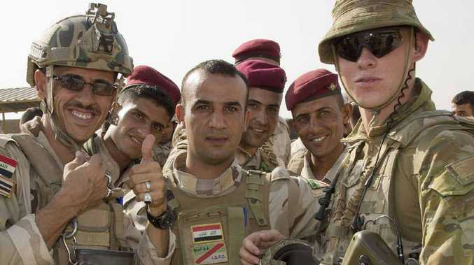 GUARDIAN ANGELS: Australian Army soldier Private Andrew Proefke stands with soldiers from the Iraqi Army while providing force protection at the Taji Military Complex, Iraq.