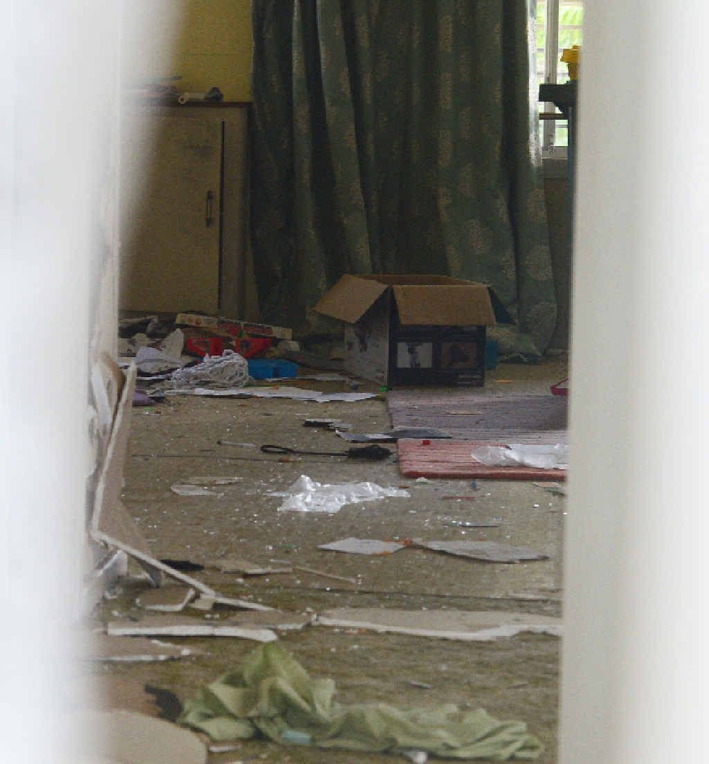 Damage shown through the window of a Simpson St home after a party.