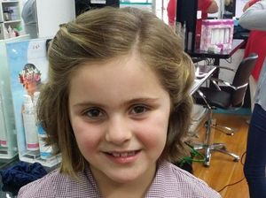 Young girl cuts long locks for cancer patients