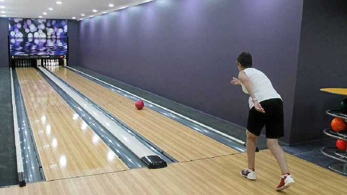 Palm Lake Resort resident Cheryl Little sends one down in the Oasis Country Club's ten-pin bowling alley. The club also has a theatre.