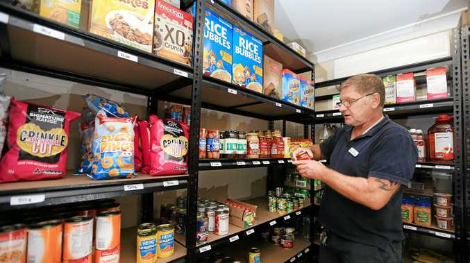 Zigi Abolitis from Nullum House Murwillumbah packs the shelves of their new food pantry which has opened to cater for the growing need of help in the community.Photo: Scott Powick Daily NewsTWE281015zigi