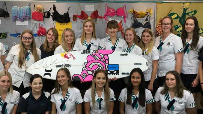 Students of Sunshine Beach State High School with the bra's they created and Julian Wilson's board. Photo Contributed