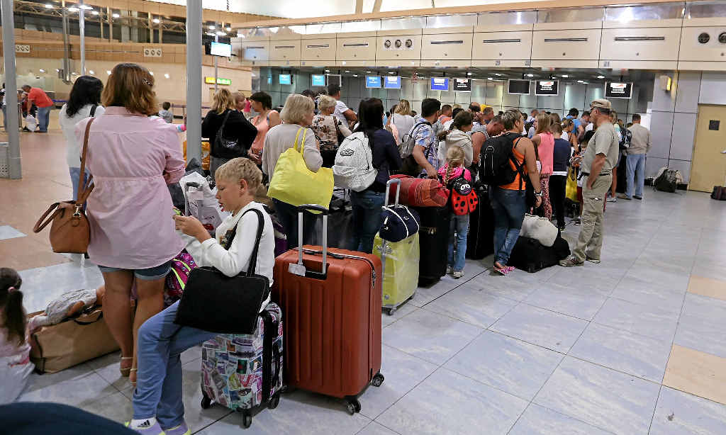 DELAYS: Russian tourists depart from Sharm el-Sheikh airport in Egypt, while (INSET) people in St Petersburg pay tribute to the 224 people who died on the Russian plane that crashed last weekend.