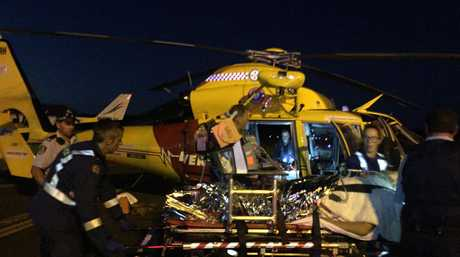 The Westpac Helicopter treating surfer Sam Morgan after he was attacked by a shark at Lighthouse Beach, Ballina, last night.