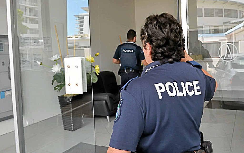 BREAK-IN: Police enter the Aurora complex yesterday.