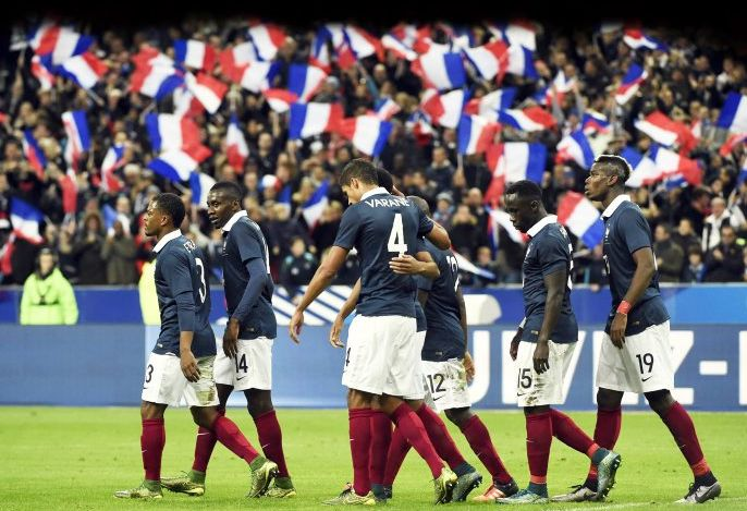France's players celebrate after opening the scoring during a friendly international football match against Germany ahead of the Euro 2016  at the Stade de France stadium in Saint-Denis, north of Paris. PhotoL AFP PHOTO / MIGUEL MEDINA