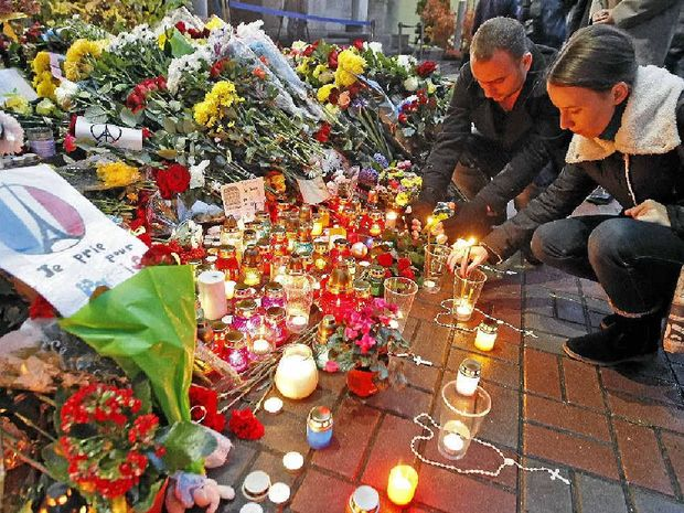 People light candles at a makeshift memorial at the French embassy in Kiev