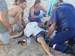 Shark attack victim Sam Morgan is treated by paramedics and an unknown woman who was one of the first on the scene at Lighthouse Beach. Photo Contributed Elton Cumming