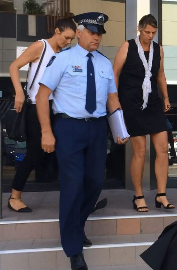Senior Constable Adam Tickner (in police uniform) leaves Maroochydore Courthouse after appearing in a Coroner's inquest into the shooting death of Edward Wayne Logan.