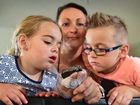 Zen Collins holds what she believes to be a meteorite that crashed through their roof in Little Mountain. The metalic chunk of rock smashed through the tin roof, the ceiling and then cracked a tile where it impacted just behind the couch. Zen and her 2 kids Scarlett, 2 and Zavier, 6 checking out the Meteorite. Photo: Che Chapman / Sunshine Coast Daily