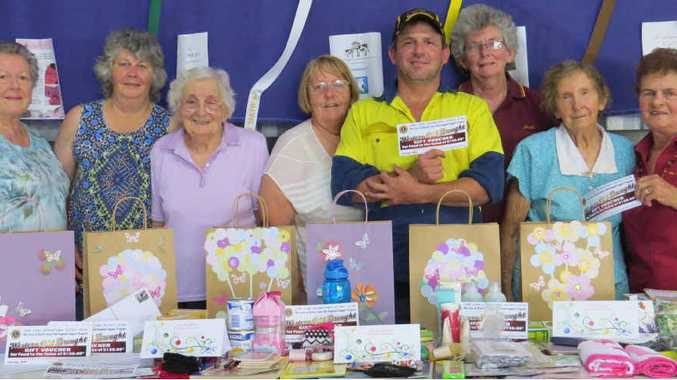 HELPING HAND: (from left) Joan Millar, Carol Robinson, Pauline Hinchliffe, Beth Jepson, Billy Geddes (President, The Caves Progress Association), Julie Clews, Doreen Pershouse, Bev Hannam (The Caves Lions Club) with decorated bags ready to be filled for distribution to drought affected families