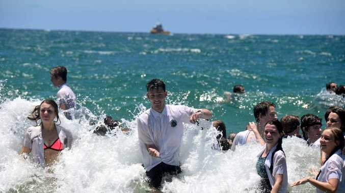 Year 12 graduates celebrate the end of their school years with a swim in their uniforms at Mooloolaba Beach.