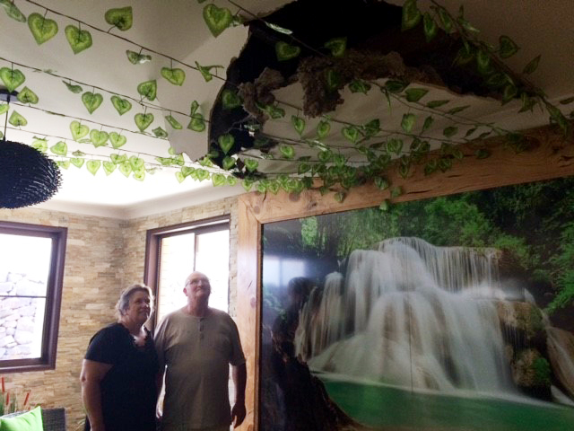 Maurie and Ruth Nielsen inspect the damage caused to their Gowrie Mountain home by a tree that fell during last night's wild storm.