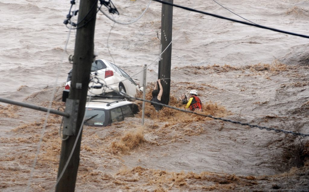 Flash flooding in Dent St. Hannah Reardon-Smith and her mother Kathryn struggling against floodwaters as an emergency services worker battled to rescue them. Photo Nev Madsen / The Chronicle