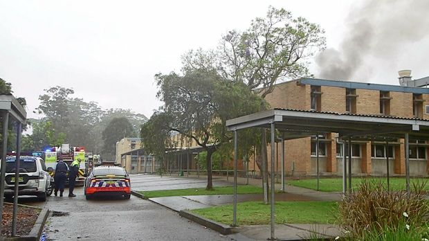 Smoke billows from the upstairs classroom in the fire at Orara High School.