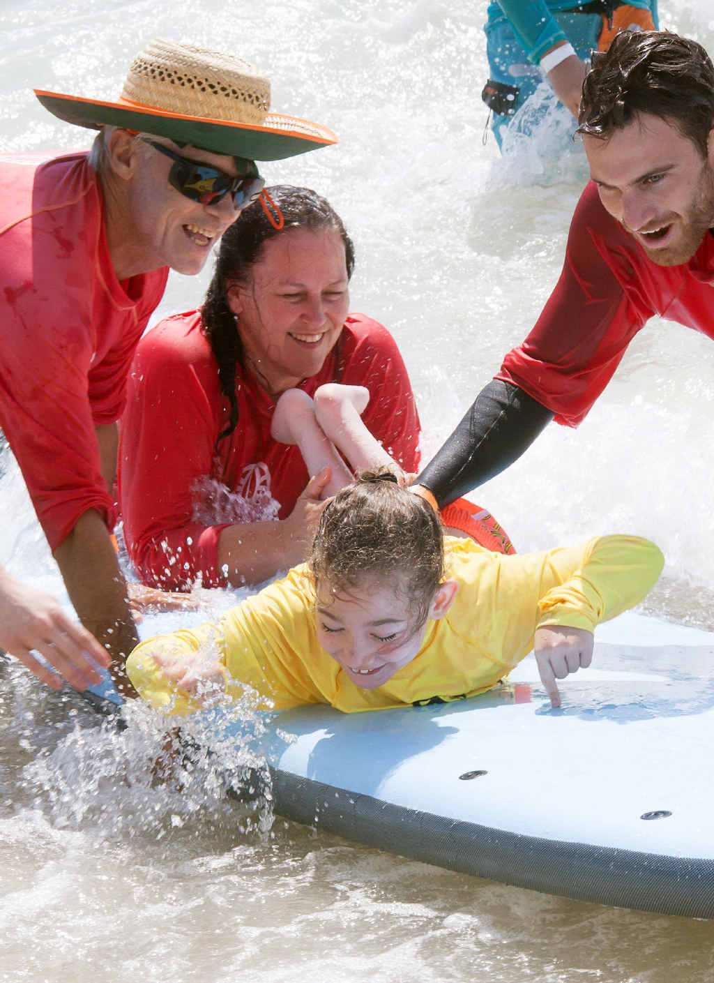 A GOOD TIME FOR ALL: Helping hands ensure Sophie Hopson gets to enjoy the feeling of surfing at Maroochydore Beach.