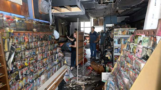Bucasia News owners Sheryl Collins and Deep Tiwana talk to fire investigators inside their shop, that was destroyed by fire. Photo Lee Constable / Daily Mercury