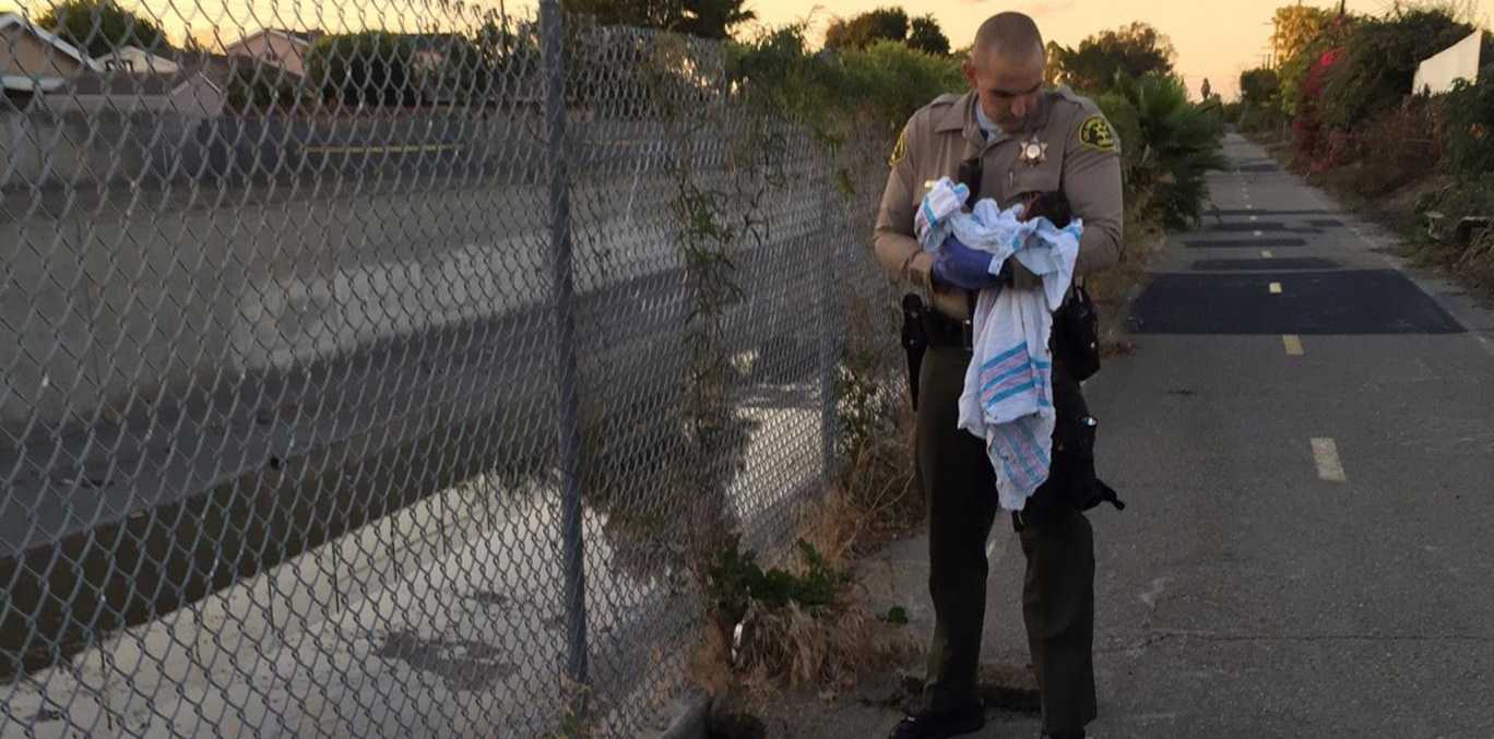Two officers removed the pieces of asphalt and debris off the baby Los Angeles County Sheriff's Department