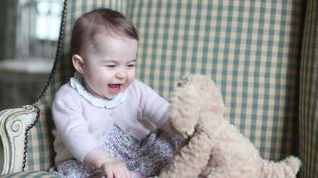 Princess Charlotte, at six months old, plays with a tiny dog toy in a photo taken by her mother the Duchess of Cambridge
